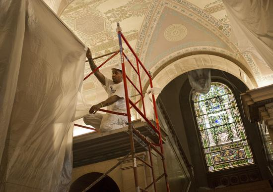 Painters cleaned detailed ceiling art by hand, using sponges and water, and then re-adhered brittle paint chips to the ceiling.