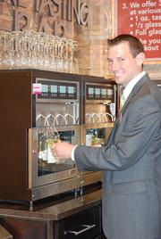 Brandon Smith, store director at the new Dierbergs in Des Peres, demonstrates the wine tasting stations.