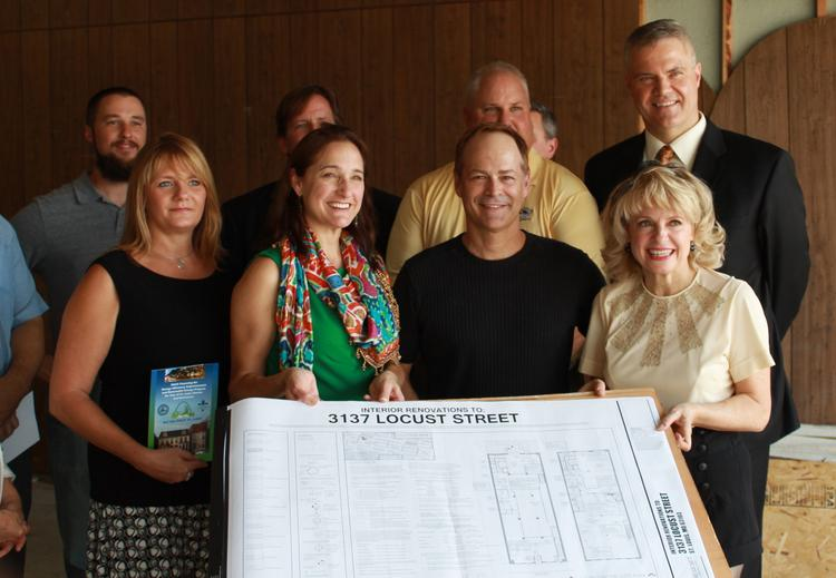 A group of investors, employees and others, including Joy Christensen (far right), holds construction plans for Tempest Distilling & Spirits Co. The distillery is expected to open in spring 2014.