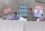 "Protesters from Westboro Baptist Church hold signs that read ""America is doomed"" and ""God hates you""."