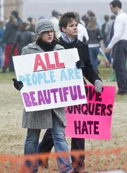 Two women hold signs promoting acceptance during a protest at Clayton High School.