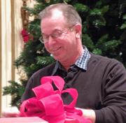 A Macy's visual expert ties a ribbon on a red present inside Powell Hall.