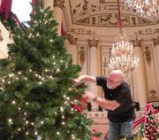 A Macy's worker adds a bit of red flare to the 12-foot Christmas tree at Powell Hall.