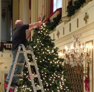 A Macy's worker adorns the top of a Christmas tree with a red Macy's star. Macy's is the sponsor of the symphony's Holiday Celebration.