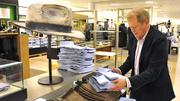 A Nordstrom employee stacks shirts.
