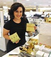 A Nordstrom employee stocks Yves Saint Laurent cosmetics.