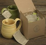 """A handmade mug fromSeeds of Happinessfeatures the company's signature """"smile."""""""
