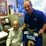 Vice President of Hockey Operations and retired Blues player Al MacInnis, right, presented Cardinals legend Stan Musial with a personalized Blues jersey.