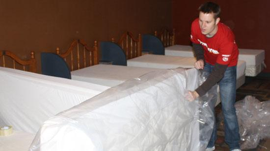 Nik Brym, a Mattress Firm employee, bags up one of the old mattresses in the sleeping area at the James S. McDonnell USO at Lambert-St. Louis International Airport.