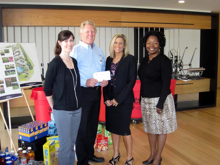 Novus International Inc. Food Drive Committee members Brittany Pham, Lisa Ervin and Gloria Ellis-Garry present a check to Frank Finnegan, president and CEO of St. Louis Area Foodbank.