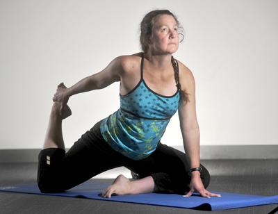 Internist Erin Bakanas benefits from both yoga and Pilates poses when she practices Yogalates in the Mind/Body Room at Saint Louis University's Simon Recreation Center.