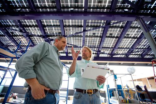 Fixture Contracting's Bill Ferebee (left) and the Moonrise Hotel's Joe Edwards discuss specifications of the 2,100-square-foot solar panel ceiling of the 'New Moon Room.'