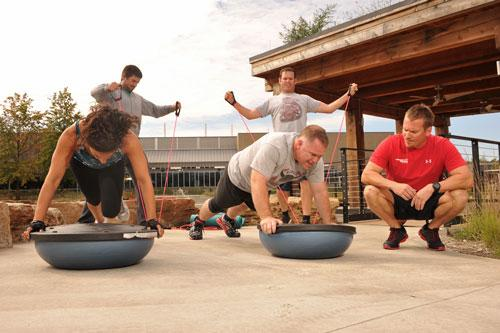 Novus employees work out under direction from trainer Shawn Fitzmaurice (right) during a workplace exercise program.