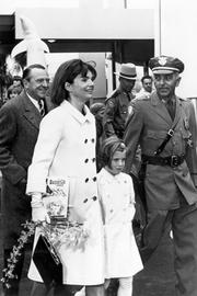 Jacqueline Kennedy carries the Gasparilla Cookbook while leaving the Florida Pavilion at the World's Fair with daughter Caroline, 1964, New York.