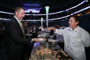 Mark Joyce from CliftonLarsonAllen picks up a couple of crab cakes from server Susan.