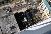 Joanie Cupler, Heartbeat International supporter, dressed as Batman to rappel off the 22-story building.