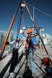 Michele Molinelli, assistant VP of claims with Brown & Brown Insurance, gets help from volunteer Bill Birdsall before rappelling from the 22-story Franklin Exchange building in downtown Tampa.