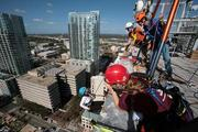 Michele Molinelli, assistant VP of claims with Brown & Brown Insurance, gets instruction from volunteer Bill Birdsall and Glenn Segrest with Heartbeat International while rappelling. Sheri Moline, with MamaRazzi Foto, takes photos.