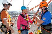 Kathleen Cabble, Tampa Bay Business Journal photographer, listens to instructions before rappelling. Glenn Segrest, site safety supervisor with Over The Edge and Wm Shrewsbury, volunteer, do the talking.