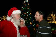 Santa and Mrs. Claus talk with Sean Miller, co-owner of Luminous Décor.