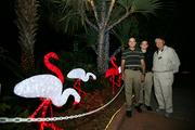 Co-owners of Luminous Décor Sean Miller and Tommy Murray with Chuck Scaffidi, president of the Florida Botanical Foundation that sponsors the annual holiday lights in the gardens program, with a lighted flamingo flock.