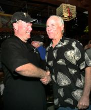 Co-owner James Morgan congratulates Brad Carlton after he downed three wings.
