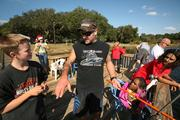 """Weekend volunteer Travis Lofland, one of the stars with TV show """"Deadliest Catch,"""" helps campers with their fishing skills."""