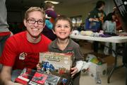 A day counselor helps his camper with his Christmas gifts he chose for his family and himself after shopping a room full of donated gifts.