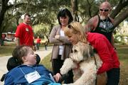 Camper Connor Hernandez visits with therapy dog Benji and his owner, Jill Gould. Tracy Hernandez and pro-wrestler and volunteer Steve Chamberlain look on.