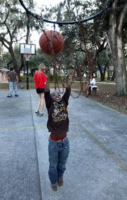 A camper shoots hoops during free time.