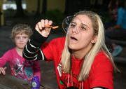 Camper Emma Holmes watches as counselor Ashley Gomez blows a bubble.