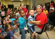 Counselor Jessica Caban and campers react when they see Santa make his entrance to hand out presents.