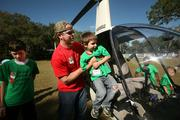 Helicopter pilot Sam Critchfield with Helicopter Academy helps camper Jeffrey Herald into the chopper. Kids got to sit in the chopper, pretend to fly and get pictures taken.