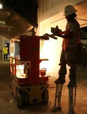 A workman on painters' stilts prepares to do wall work in the new club lounge area.