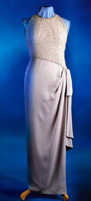 A chic, sarong inspired, evening dress of grey silk crepe, designed by Catherine Walker. Estimated at $250,000/$300,000