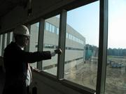 CEO Adams looks out from a second floor bank of windows looking east toward conservation land. When complete, this view will show heavily landscaped gardens amid abundant light.