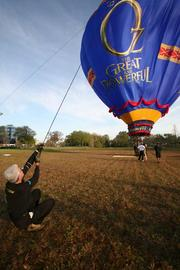 Being a balloon handler can be an excellent workout. Professional balloon crew member, Drew Barrett with Lighter Than Air out of Boise, Idaho, struggles to control the balloon as the wind picked up, pulling him about the field.