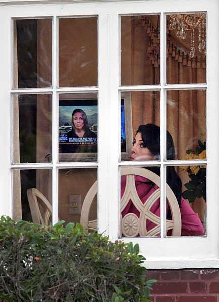 A woman fitting the description of Tampa's Jill Kelley watches Fox News Channel in the Kelleys' home on Bayshore on Tuesday as media from around the country lined up on the sidewalk around the corner.