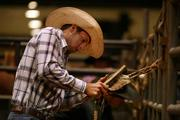 A cowboy readies his equipment during the rodeo.
