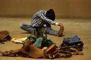 J.C. DeSaveur from Roberts, Mont., stretches before the saddle bronc riding competition.