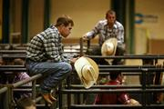 Justin Caylor from Andalusia, Ala., sits near the shoots waiting for the saddle bronc riding competition to start.
