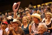 Beverly Sneed from Tampa waves her pink cowboy hat and people laugh in response to the rodeo clown and the announcer's funny questions.