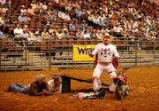Rodeo clown Justin Rumford rode his mini motorcycle up the ramp and over the men on the ground.