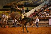 Caleb Martin from Sulphur, La., during the saddle bronc riding event. She was the only female competitor in the rodeo aside from the women in the barrel racing event.
