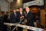 Tim Juul, manager of food and beverage for HMSHost at Tampa International Airport, Tom Fricke, president and CEO of HMSHost Corp., and Richard Gonzmart, president of Columbia Restaurant, cut the ribbon outside the new airport restaurant location.