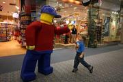 """At the Tampa International Airport location of Mindworks and Ron Jon Surf Shop, """"Lego Man"""" greets 3-year-old Jaydin Nielsen."""