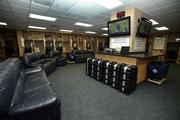 The players' clubhouse waits for opening day. It is filled with hanging jerseys, rows of cleats, couches and TVs.