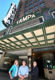 "The iconic ""Tampa"" blade sign outside the building plays an important role in the overall brand of the Tampa Theatre. From left are Jill Witecki, Tampa Theatre director of marketing and community relations, John Bell, the theater's president and CEO, and David Capece, CEO of Sparxoo."
