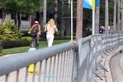 People walking to work and people exercising dodge security gates around the Tampa Bay Times Forum.