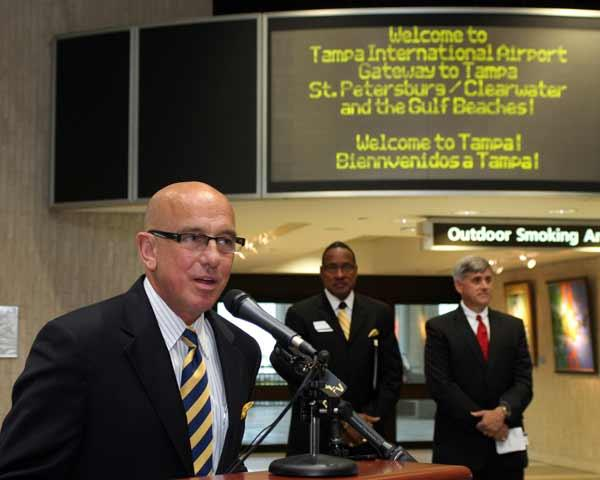 Tampa International Airport CEO Joe Lopano speaks at the airport during an event, with a welcome sign behind him.
